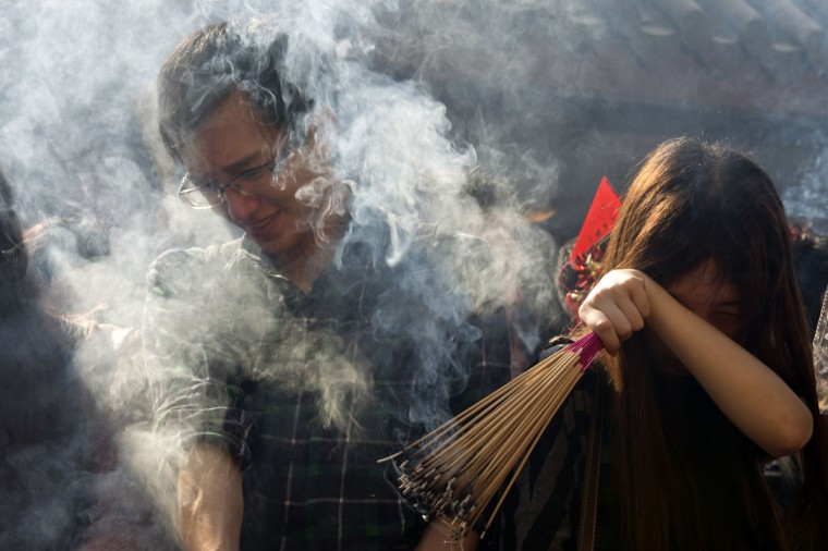 Worshippers are covered in thick smoke from burning incense sticks as people marked the third day of the Lunar New Year holiday at Che Kung Temple in Hong Kong on February 2, 2014. Chinese communities across Asia came together to usher in the Year of the Horse, with tens of thousands of worshippers flocking to temples across China to pray for good fortune in the new year. (Alex Ogle/AFP/Getty Images)