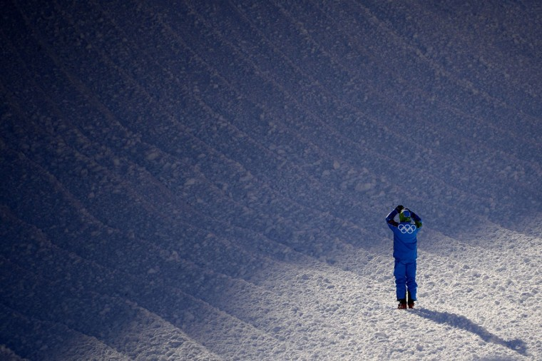 A volunteer takes a photo of the Women's downhill slope at the Rosa Khutor Alpine Center in the mountain cluster on February 2, 2014, prior to the start of Sochi Winter Olympic Games. (Olivier Morin/AFP/Getty Images)