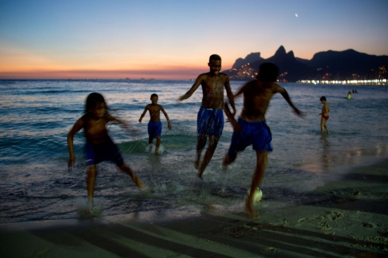 Youth from the Cidade de Deus shantytown play football at Ipanema Beach at sunset in Rio de Janeiro, Brazil on February 1, 2014. (Christophe Simon/AFP/Getty Images)