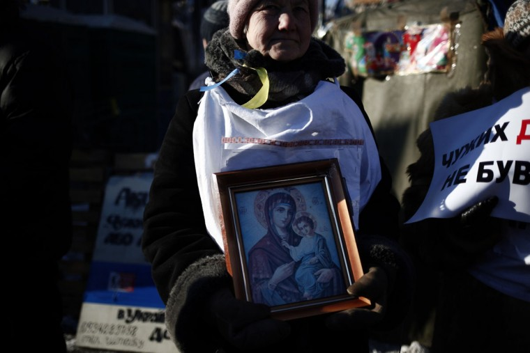 An anti-government protester holds a picture of Virgin Mary in Independence Square during a demo in Kiev on February 2, 2014. Ukraine's opposition said it had requested financial aid from Western powers that have pledged support for the protest movement against President Viktor Yanukovych. (Angelos Tzortzinis/AFP/Getty Images)