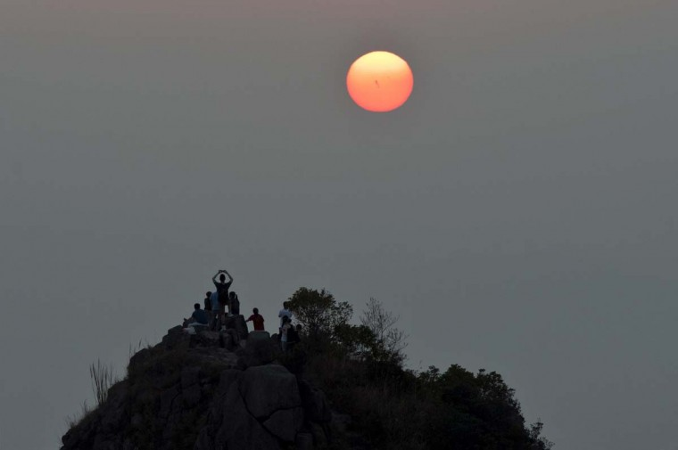 A man, among a group of hikers, takes a photo of the setting sun in Hong Kong on the fourth day of the Lunar New Year holiday on February 3, 2014. Chinese communities across Asia came together to usher in the Year of the Horse, with tens of thousands of worshippers flocking to temples across China to pray for good fortune in the new year. (Alex Ogle/AFP/Getty Images)