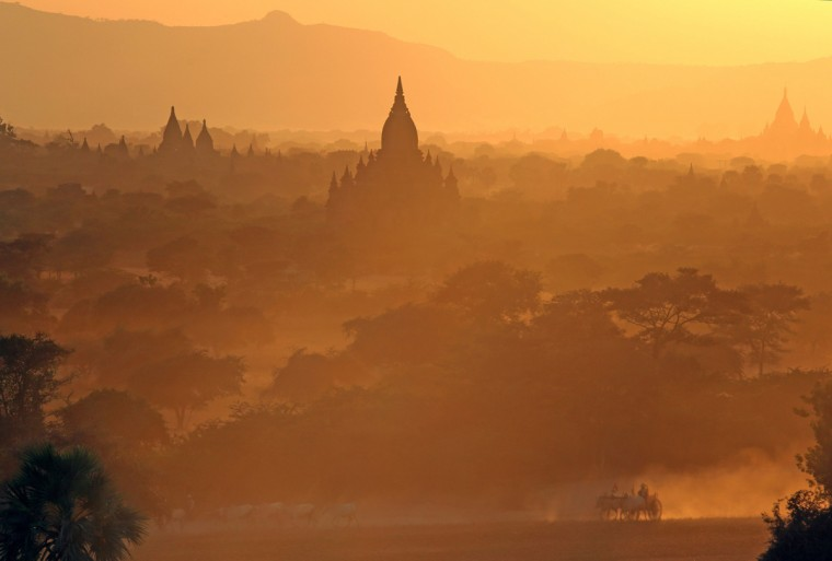 In this picture taken February 3, 2014, people are transported on cattle drawn cart as they pass in front of the ancient pagodas at Bagan, Myanmar. (Ye Aung Thu/AFP/Getty Images)