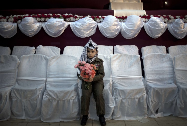 A young Palestinian girl wearing a traditional Keffiyeh head scarf carries a flower bouquet ahead of a mass wedding ceremony in Gaza City on February 4, 2014. (Mahmud Hams/AFP/Getty Images)
