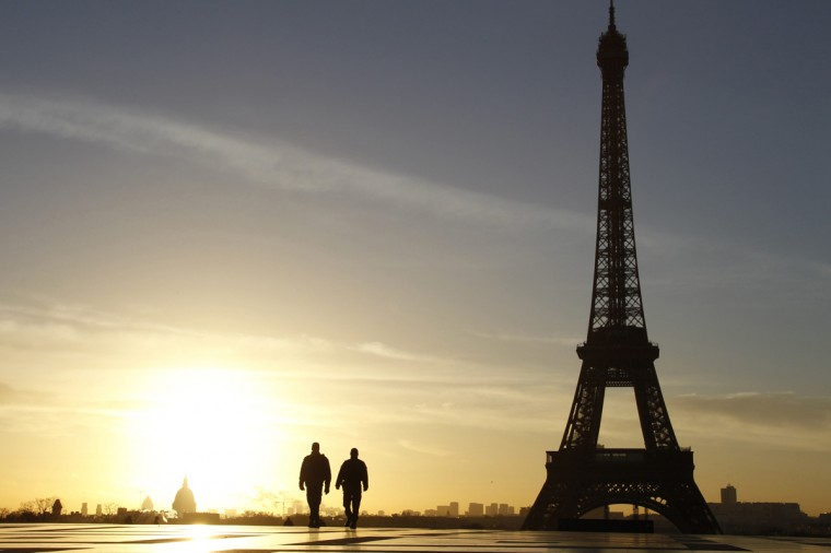 A picture taken on February 11, 2014 shows people walking at sunrise on the Trocadero Esplanade, also known as the Parvis des droits de l'homme (Parvis of Human Rights), in front of the Eiffel Tower in Paris. (Ludovic Marin/AFP/Getty Images)
