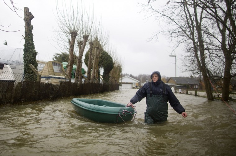 A man pulls a boat through floodwaters as he sets off to collect food in Thames Meadow, near Shepperton, south of London on February 11, 2014. Flooding in Britain spread along the River Thames and began to threaten London on Monday, as a political row over the handling of devastating winter storms erupted into the open. (Justin Tallis/AFP/Getty Images)