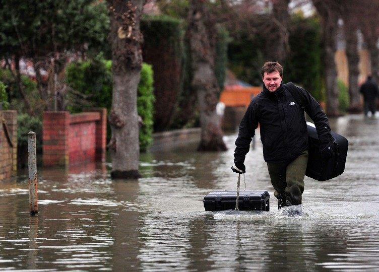 A man drags his possessions in a peli-case as he wades along a flooded road near Staines, west of London on February 12, 2014. Flooded communities in Britain faced a fresh battering from storms and high winds as emergency efforts in stricken areas picked up following criticism of a sluggish response. (Carl Court/AFP/Getty Images)