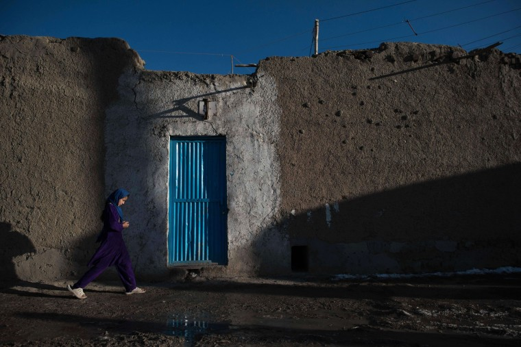 "An Afghan girl walks past a residence near Shuhada lake in Kabul on February 12, 2014. Some nine million Afghans or 36 percent of the population are living in ""absolute poverty"" while another 37 percent live barely above the poverty line, according to a UN report. (Nicolas Asfouri/AFP/Getty Images)"
