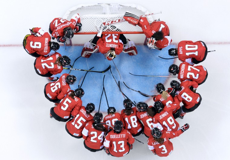 Canada's player gather before the start of the Women's Ice Hockey Group A match between Canada and USA at the Sochi Winter Olympics on February 12, 2014 at the Shayba Arena. (Jonathan Nackstrand/AFP/Getty Images)