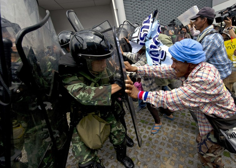 Thai farmers battle with soldiers as they protest the government's repeatedly delayed payments for rice submitted to the pledging scheme at the government's temporary office in Bangkok on February 17, 2014. Thai opposition demonstrators besieged government offices on February 17, including a compound that has been used as a temporary headquarters by Prime Minister Yingluck Shinawatra, in defiance of authorities who have vowed to reclaim key state buildings. (Pornchai Kittiwongsakul /AFP/Getty Images)