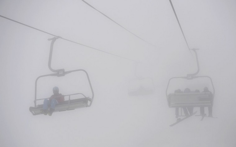 Snowboarders and skiers take the ski-lift in heavy fog at the Rosa Khutor Extreme Park during the Sochi Winter Olympics on February 17, 2014. Heavy fog is forcing Olympic organizers to postpone some events. (Franck Fife/AFP/Getty Images)