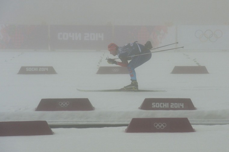 A Russian skier warms up as fog descends at the Laura Cross-Country Ski and Biathlon Center. The men's biathlon 15-km mass start was postponed due to heavy fog. (Alberto Pizzoli/AFP/Getty Images)