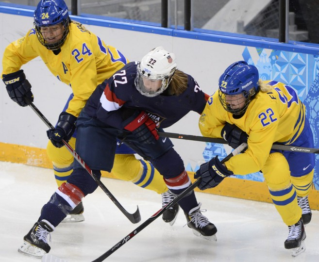 Kacey Bellamy (center) of the U.S. vies with Sweden's Emma Eliasson (right) and Sweden's Erika Grahm during the women's ice hockey semifinals at the Shayba Arena during the Sochi Winter Olympics on February 17, 2014. (Jonathan Nackstrand/AFP/Getty Images)