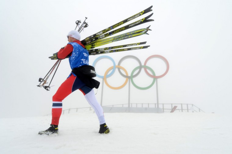 An athlete carries skis at the Laura Cross-Country Ski and Biathlon Center on February 17, 2014. Thick fog shrouding the mountains at the Sochi Olympics forced organizers to postpone biathlon and snowboard cross events. (Kirill Kudryavtsev/AFP/Getty Images)