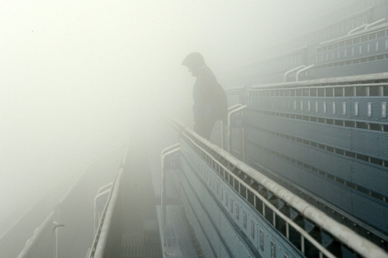 A spectator stands on the tribune as fog descends on the Laura Cross-Country Ski and Biathlon Center during the Sochi Winter Olympics on February 17, 2014, in Rosa Khutor, near Sochi. Due to weather conditions the men's biathlon mass-start 15-kilometer race has been postponed. (Kirill Kudryatsev/AFP/Getty Images)