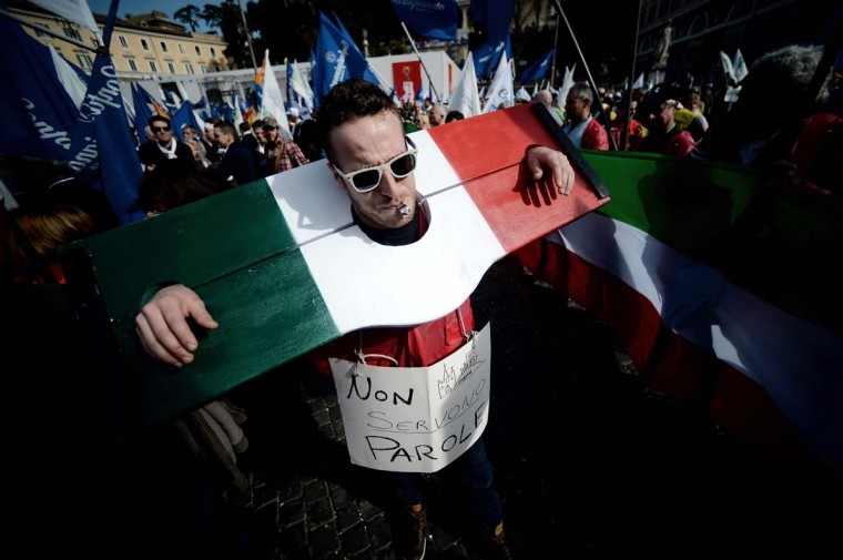 A protestor with his head and hands trapped in pillory bearing the colours of the Italian flag takes part in a demonstration in downtown Rome's Piazza del Popolo on February 18, 2014. Artisans and merchants from all over Italy arrived in Rome to demand that Parliament the new government in the midst of being formed make an urgent breakthrough in economic policy after the economic crisis shut down more than 372 000 businesses in 2013. (Filippo Monteforte /AFP/Getty Images)