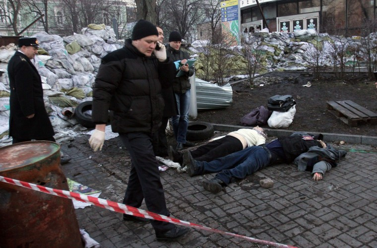 Police experts examine bodies of the dead anti-government protesters after their clashes with the police in Kiev on February 18, 2014.Ukrainian riot police stormed the main opposition camp in Kiev Tuesday after clashes left at least seven dead in the bloodiest day in three months of protests, triggering international alarm. (Anatoli Boiko/AFP/Getty Images)