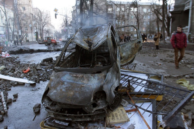Burnt out vehicles remain after protesters clashes withpolice in Kiev on February 18, 2014. Police on Tuesday fired rubber bullets at stone-throwing protesters as they demonstrated close to Ukraine's parliament in Kiev, an AFP reporter at the scene said. Police also responded with smoke bombs after protesters hurled paving stones at them as they sought to get closer to the heavily-fortified parliament building. (Anatolii Boiko/AFP/Getty Images)