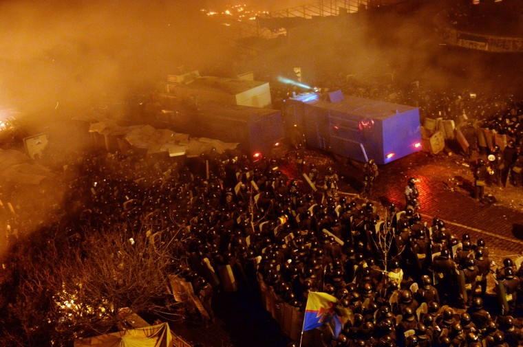 Anti-government protesters clash with the police during their storming of Independence Square in Kiev on February 18, 2014. Flames engulfed the main anti-government protest camp on Independence Square on Tuesday as riot police tried to force demonstrators out following the bloodiest clashes in three months of protests. The iconic square turned into a war zone as riot police moved slowly through opposition barricades from several directions, hurling stun grenades and using water cannon to clear protestors. (Sergei Supinsky/AFP/Getty Images)