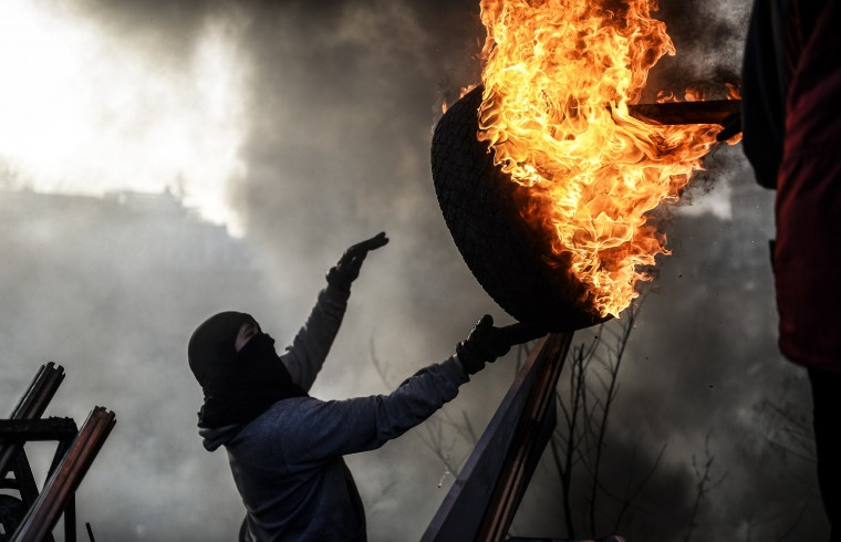 An anti-government demonstrator holds a burning tire as he build a barricade on February 21, 2014 at the Independent square in Kiev. Armed protesters stormed police barricades in Kiev on Thursday in renewed violence that killed at least 26 people and shattered an hours-old truce as EU envoys held crisis talks with Ukraine's embattled president. Bodies of anti-government demonstrators lay amid smouldering debris after masked protesters hurling Molotov cocktails and stones forced police from Kiev's iconic Independence Square -- the epicentre of the ex-Soviet country's three-month-old crisis. (Bulent Kilic/AFP/Getty Images)