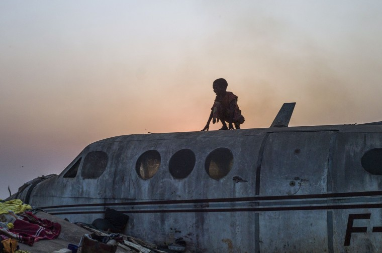 "A boy stands on an airplane in the Christian Mpoko refugee camp on February 20, 2014 during sunset, in Bangui, Central African Republic. Interim President Samba Panza has vowed to ""go to war"" on the anti-balaka, who claim to seek vengeance for atrocities committed by a mainly Muslim rebel alliance, the Seleka, which temporarily seized power in March last year. The Seleka coup plunged the country into chaos, unleashing a wave of Muslim-Christian violence that has left thousands dead. Hundreds of thousands of people have also been displaced by the brutal surge of killings, mutilations, rapes and looting. (Fred Dufour/AFP/Getty Images)"