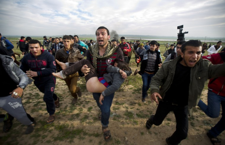 Palestinian civilians carry an injured boy during clashes with Israeli security forces near the eastern border of the Gaza Strip, east of the northern town of Jabalia, on February 21, 2014 following a demonstration demanding for the lifting of the Israeli blockade on the Palestinian enclave. The territory has been languishing under an Israeli blockade since 2006 after Gaza militants snatched an Israeli soldier who was released in a prisoner swap deal in 2011. (Mahmud Hams/AFP/Getty Images)