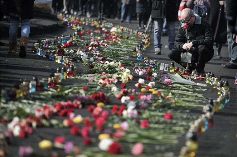 """People add flowers to a huge line of flowers and candles leading to the barricades in central Kiev on February 24, 2014. Ukraine issued an arrest warrant for ousted president Viktor Yanukovych on Monday as the country's new rulers launched a probe over the """"mass murder"""" of protesters in a week of carnage in Kiev.(Louisa Goulisamaki/AFP/Getty Image)"""