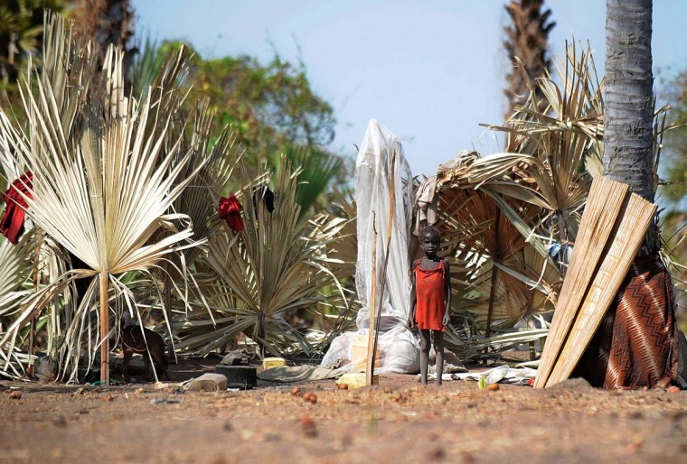 A young girl from the Nuer tribe in South Sudan stands on February 21, 2014 outside a makeshift compound demarcated using palm fronds that also serves as their shelter on one of the islands in the Sudd swamplands in Unity state, central South Sudan. Thousands of Nuer tribes people are believed to have fled into the swamplands around Nyal district after around 1,200 soldiers and a small army of young men swarmed, on February 7, Panyijiar county to carry out a killing, looting and razing spree that left 60 dead and 26 wounded. In Panyjiar, an overwhelmingly Nuer area bordered by a Dinka majority, the only place to hide is the swamp, after a power struggle between leaders in the new nation's capital Juba in mid-December revived old ethnic tensions between South Sudan's largest Dinka tribe and secondary Nuer tribe. (Tony Karumba/AFP/Getty Images)