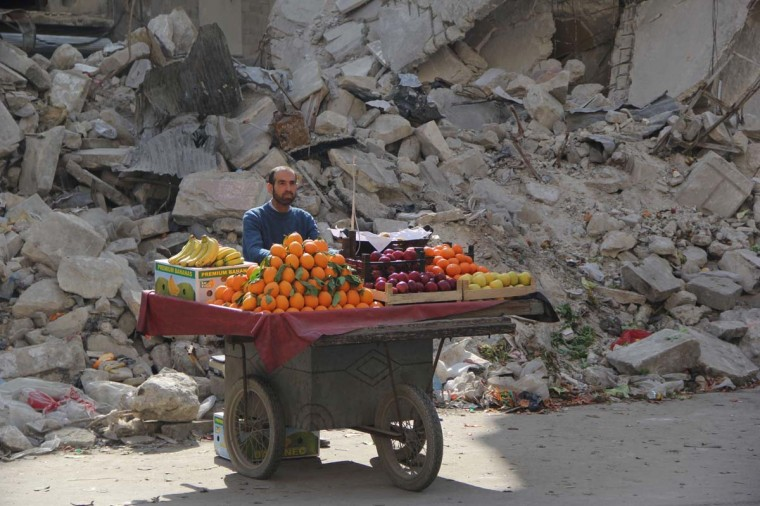 A Syrian fruit vendor waits for customers next to a damaged building on February 24, 2014 in the Shaar neighborhood of the northern city of Aleppo. More than 140,000 people are estimated to have been killed in Syria's nearly three-year war, and millions more have been forced to flee their homes. (Mohammed Al Katieb/AFP/Getty Images)