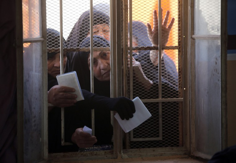 Iraqi women wait behind a window to receive their electronic voter ID cards in the capital Baghdad on February 25, 2014, ahead of legislative elections in April. (Ahmad Al-Rubaye/AFP/Getty Images)