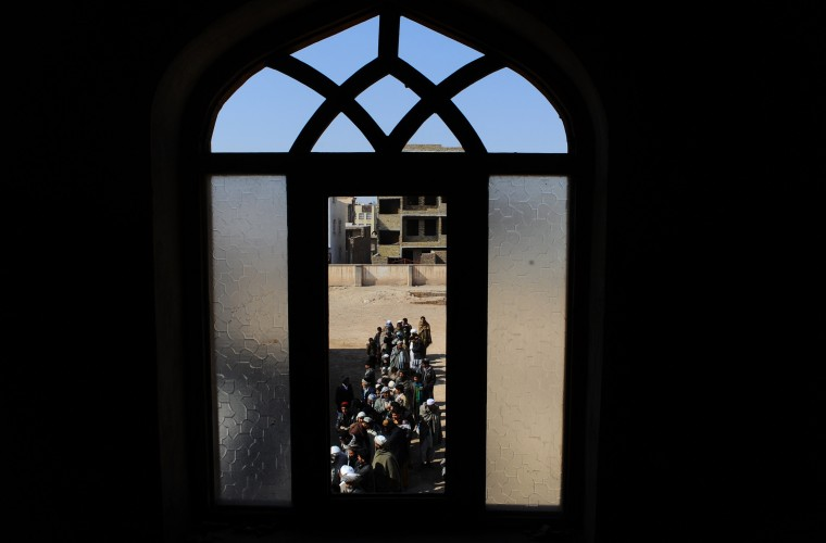 Afghan men wait in line outside a voter registration centre in Herat province on February 26, 2014. Afghanistan is due to hold presidential and provincial council elections in April this year. (Aref Karimi/AFP/Getty Images)