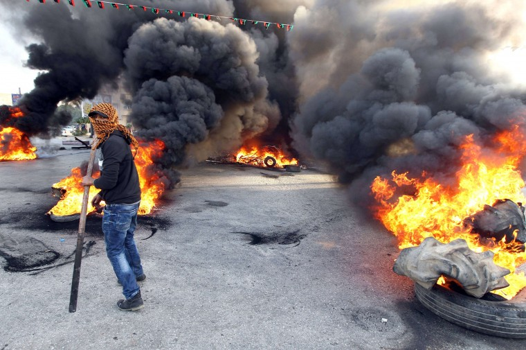 """A protestor walks in front of burning tyres as they block a street in Libya's second city of Benghazi on February 26, 2014 after the killings of two policemen. The fatal shootings of the two officers -- one serving, one retired -- came just a day after the UN mission in Libya voiced """"deep concern"""" over the near-daily violence plaguing the North African country, particularly the east. (Abdullah Doma/AFP/Getty Images)"""