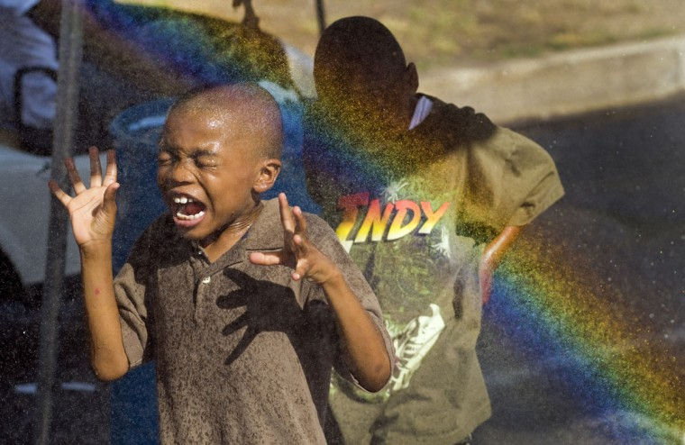 Nasser Lee, 7, of Baltimore leads his older brother Najee, 8, through the misting tent that produces an afternoon rainbow in the summer heat during the first day of Artscape July 16, 2010. (Karl Merton Ferron / Baltimore Sun Staff)