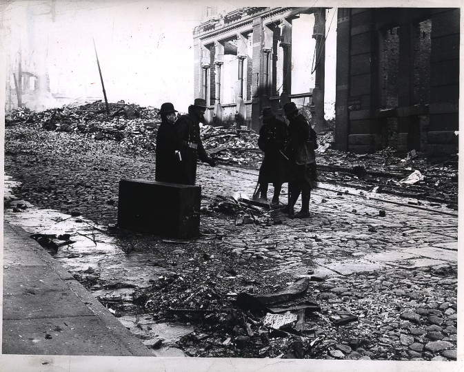 On Lombard Street near Cypress Alley, Guardsmen warm themselves at a fire built of wreckage. Morning of February 11. Photographer unknown.