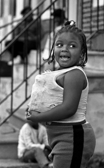 Baltimore, MD --1988 -- Peaches Loving, age 4, pretended to be pregnant by stuffing crumpled paper under her shirt. In the late 1980's, Baltimore had the highest rate of teen pregnancy of any major city in the United States. This image is from an extended photo essay on a young teen mother who lived near this little girl. (Amy Davis / Baltimore Sun)