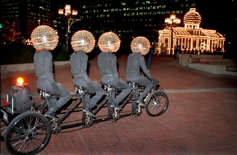 """Baltimore, MD - 1987 -- Artist Eric Staller and three students from the Maryland Institute, College of Art, appear to be extra-terrestials going home, as they cycle toward """"Santa's Place"""" at Baltimore's Inner Harbor. I was following the performance artists as they pedaled downtown, and was struck by the amusing connection between the building and the """"Bubbleheads."""" (Amy Davis / Baltimore Sun)"""