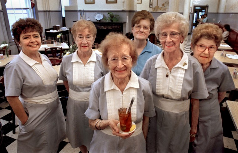 Baltimore, MD - 1995 -- The venerable waitresses at the Woman's Industrial Exchange, from left, are Trish Hall, 57, Loretta Tarbert, 80, Marguerite Schertle, 94 (holding ice tea), Charlotte Zimernack, 68, Carrie Geraghty, 88, and Margaret Brogna, 84. These women knew that they represented a vanishing era. I could not keep up with Marguerite as she whizzed around the dining room serving iced tea, chicken salad and tomato aspic. (Amy Davis / Baltimore Sun)