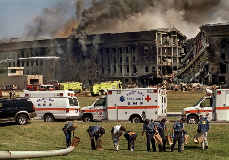 Washington, D.C. - 2001 - FBI agents methodically combed the Pentagon grounds for evidence from the terrorist plane attack on 9/11, while firefighters battled the flames inside the massive complex. It was very difficult to gain access to this scene, and while I was darting around trying not to get caught, I couldn't believe what I was seeing. (Amy Davis / Baltimore Sun)