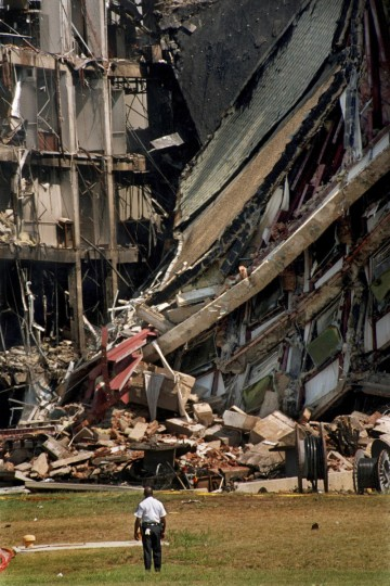Washington, D.C. - 2001 -- An officer is dwarfed by the massive destruction caused by the terrorist plane attack on the Pentagon on 9/11. A book, still open on a table stand on the third floor, is a reminder of the lives lost in the debris. I was listening to the unbelievable news of the World Trade Center attacks while heading to an Eastern shore assignment, and was on the Bay Bridge when I heard about the attack on the Pentagon. As soon as I crossed the bridge, I made the fastest U-turn I could manage, and headed to D.C. (Amy Davis / Baltimore Sun)