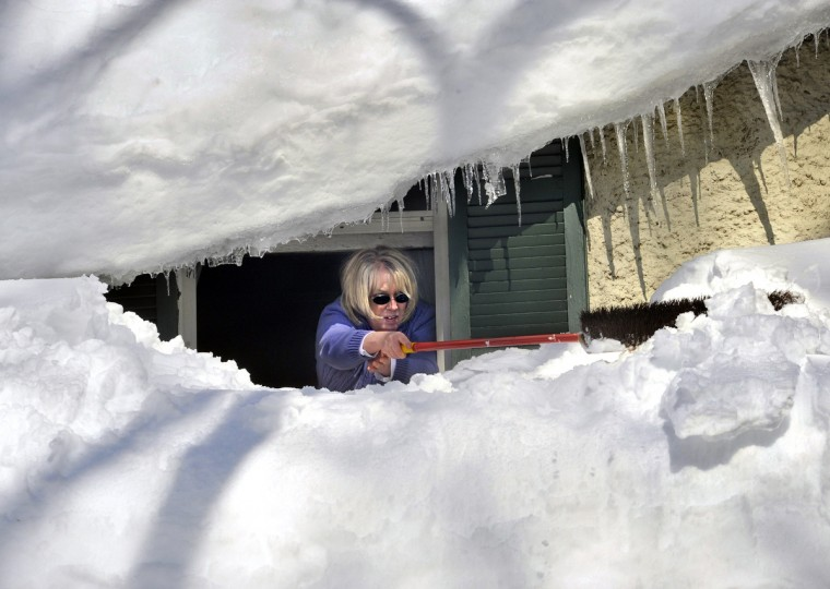Baltimore, MD - 2010 -- Rebecca Girvin leans out the second floor window of her home in the Lake-Walker neighborhood to push snow off her front porch roof. She had trouble extending the broom far enough to push the snow over the edge of the roof. This snowfall brought the total snow accumulation in Maryland for the winter of 2010 to a record-breaking 79 inches. Luckily I found this scene near my home, since my car was snowed in and I was traipsing around on foot and transmitting photos from home. (Amy Davis / Baltimore Sun)