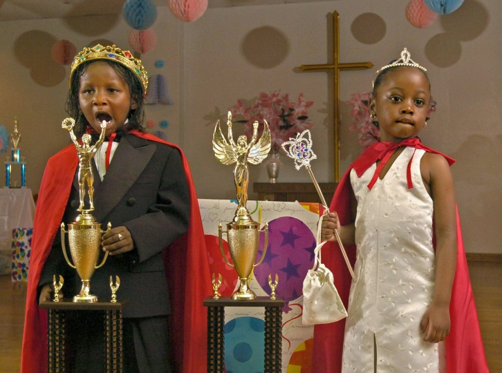 "Baltimore, MD - 2004 -- After being crowned, ""King"" Hisheen Humphrees, left, yawned as he and ""Queen"" Shon'Tia Crawford, both 4, posed with their trophies at the Pre-Kindergarten King and Queen Prom, created to build self-esteem for inner city children. The pride of the teachers and parents, who created elegant miniature outfits and fanciful room decorations, was a touching testament to their love for these pre-schoolers, who seemed a little dazed by the experience. (Amy Davis / Baltimore Sun)"