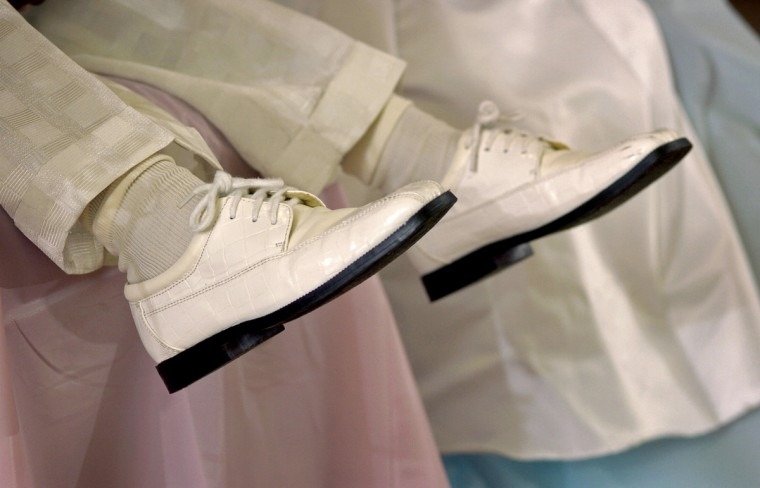 """Baltimore, MD - 2004 -- Antoine James, 5, had shiny, grown-up off-white shoes to match his suit, but his feet couldn't reach the floor. The 4th annual Pre-Kindergarten King and Queen Prom, held at Pennsylvania Avenue AME Zion Church, was organized by Harlem Park E.S. Pre-K teachers Helen Froneberger and Cynthia Lewis for their students, with help from school staff and parents. 23 elegantly-dressed Pre-K students, with """"escorts"""" and relatives, came to the highly-anticipated event. (Amy Davis / Baltimore Sun)"""
