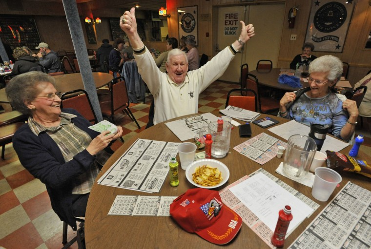 """Rosedale, MD -- 2011 -- Bill James, 80, of Rosedale, center, celebrates after winning $95 in a """"full card"""" game, as his wife Mary James, 76, left, and friend Thelma Sutphin, 68, of Middle River, look on, at VFW Post 6506. The VFW Post wanted to hold casino nights with card games and roulette to raise more money, if the legislature approved an expansion of gambling. (Amy Davis / Baltimore Sun)"""