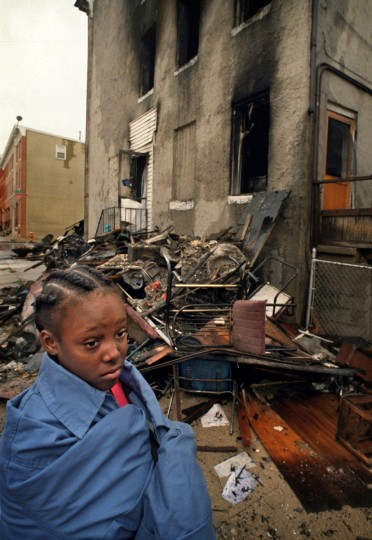 Baltimore, MD - 2002 - After Angela and Carnell Dawson repeatedly stood up to drug dealers, their rowhouse was firebombed in retaliation, killing both parents and five of their children. The tragedy outraged the community and raised the issue of witness intimidation. I had returned to the office with photos of the immediate aftermath of the fire, and our Photo Director Bob Hamilton asked me to return a little later. There I found a neighbor, 10-year old Marilyn Johnson, who knew all the young victims. She was standing vigil because she believed that the children were still under the rubble. I tried to reassure her that her playmates had been removed, but the whole situation was very heartbreaking. (Amy Davis / Baltimore Sun)