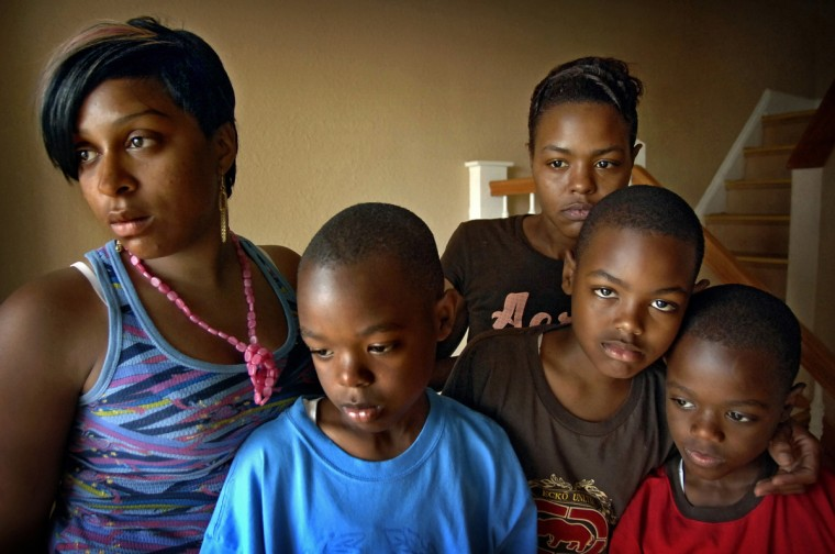 Baltimore, MD - 2007 -Donneka Tate, left, and her sister, Danyelle Davis, right, with Danyelle's three sons, from left, Antrel, Antar, and Antae McDowell, await the arrival of other relatives as they grieved the death of the sisters' grandmother, who had been stabbed to death in her apartment by a homeless man she had been helping. These are very difficult situations to intrude upon with a camera, so I try to work as simply and gently as I can. (Amy Davis / Baltimore Sun)