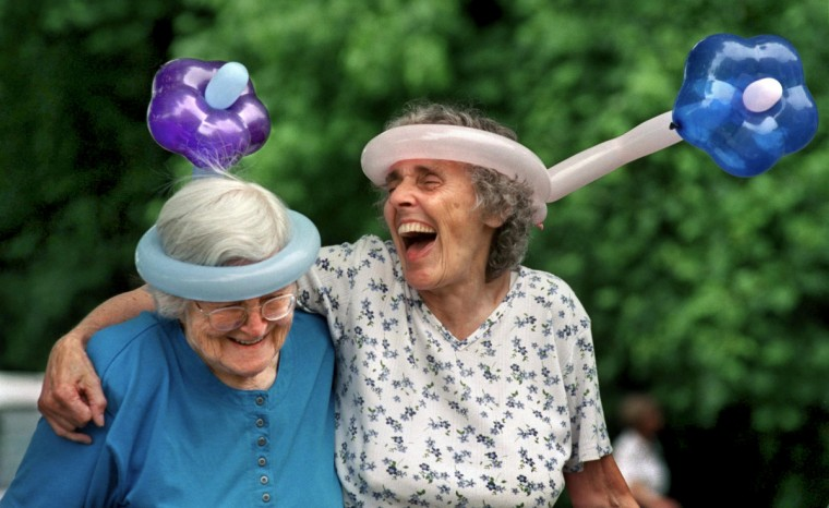 """Arnold, MD - 2001 -- Stella Rohde, 83, left, and her long-time friend, Laura Tucker, 75, kept each other laughing at an Expo for seniors. Rohde, acknowledging their silly hats, explained, """"It's not that we're crazy. It's just that we don't give a damn!"""" A telephoto lens separates the women from the background by blurring the shrubs, which emphasizes their balloon hats. A long lens also helps in capturing candid moments without the subjects becoming self-conscious. (Amy Davis / Baltimore Sun)"""