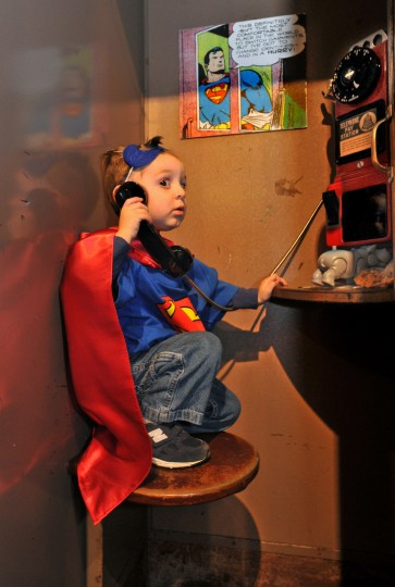 "Baltimore, MD-2013- Lucas Taylor, 2, of Columbia listens to a message for Batman in a vintage phone booth at ""Zap! Pow! Bam! The Superhero, 1938 - 1950,"" an exhibit at The Jewish Museum of Maryland. His parents and I were amused that Lucas and the other children who tried out the old-fashioned phone had no idea what a phone booth was. (Amy Davis / Baltimore Sun)"