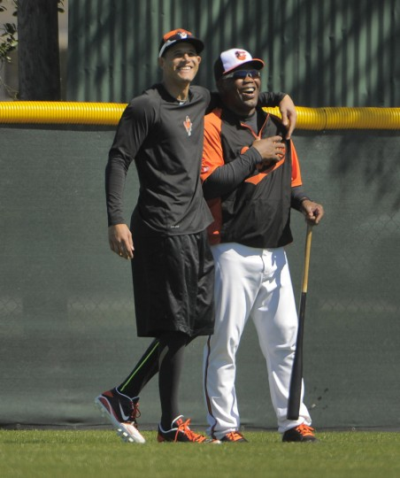 Rehabilitating from a 2013 injury, Orioles third baseman Manny Machado (left) smiles with first base coach Wayne Kirby in the outfield during workouts at the club's spring training facility. (Karl Merton Ferron/Baltimore Sun)