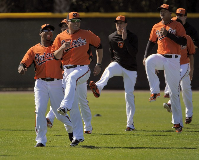 Orioles left fielder Francisco Peguero (left) and catcher Johnny Monell limber up shoulder-to-shoulder in front of third baseman Manny Machado (background right, in black) during the first official day of workouts with the full squad. (Karl Merton Ferron/Baltimore Sun)