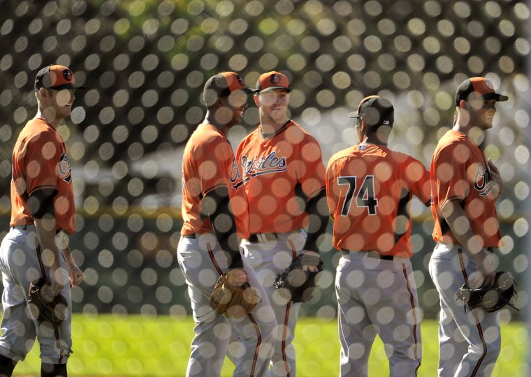 Orioles pitchers are framed by fencing as they participate in fielding drills. (Karl Merton Ferron/Baltimore Sun)