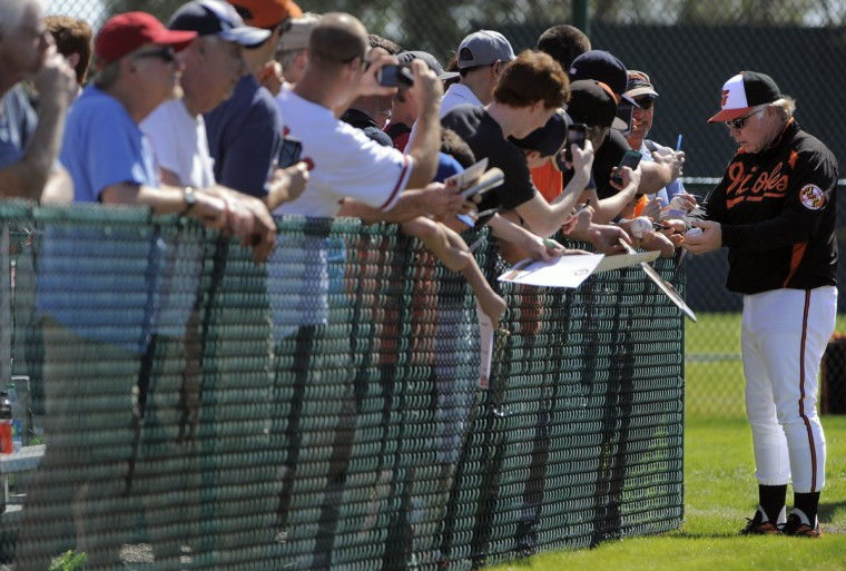 Orioles manager Buck Showalter signs autographs for fans during a workout at the club's spring training facility. (Karl Merton Ferron/Baltimore Sun)